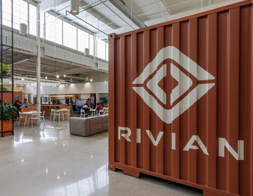 A high-ceilinged office space with many windows. In the the foreground, there is a shipping container with the logo for Rivian.