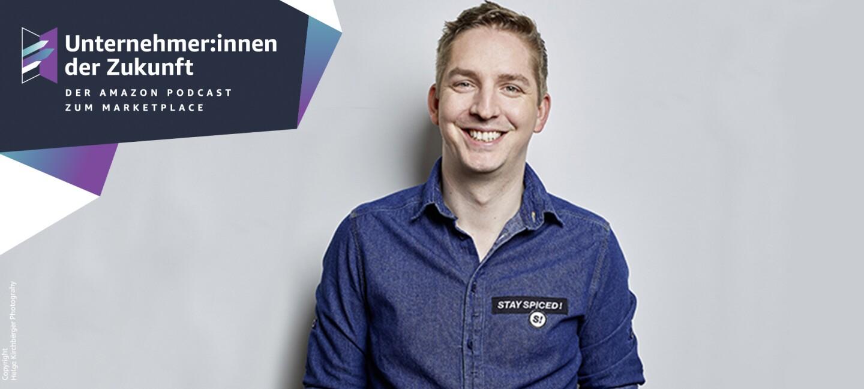 """Ein Mann mit kurzen dunklen Haaren und einem Jeans-Hemd lacht in der Kamera. Der Schirftzug """"Unternehmer:innen der Zukunft"""" ist links eingeblendet."""
