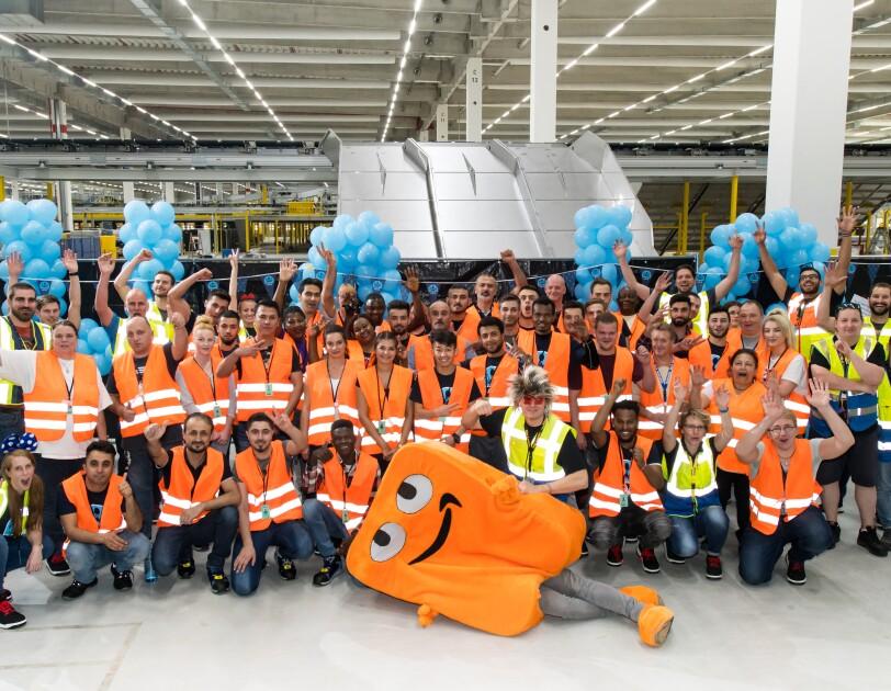 Gruppenbild der Mitarbeiter mit Maskottchen Peccy: Die Mitarbeiter tragen Sicherheitswesten, ein Mitarbeiter trägt das Peccy-Kostüm, das in orangener Farbe an einen Karton erinnert.