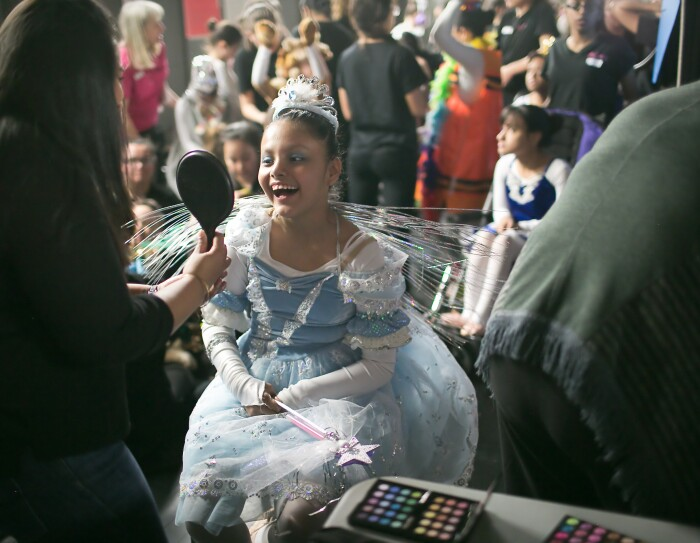 A girl in a princess dress looks into a small handheld mirror after getting her makeup done for a dance performance. Many other performers are shown in the background.