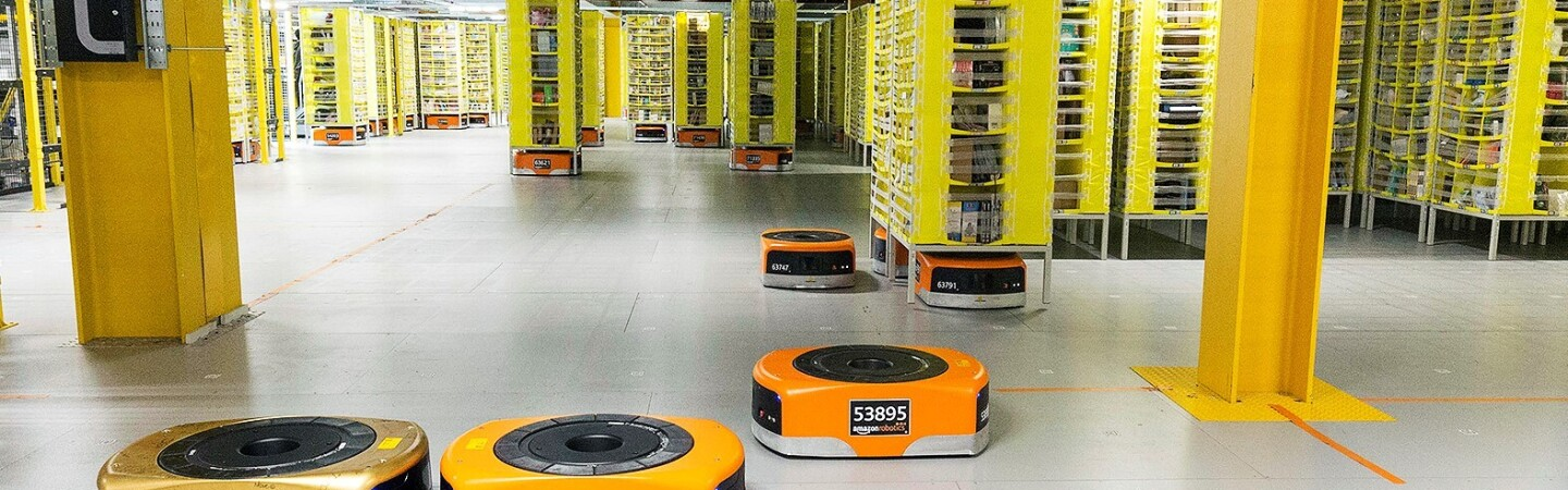 Several orange robots are pictured in a Fulfillment Center as they help move products across the floor.