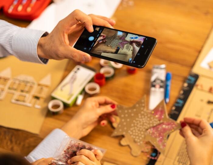 En una mesa de madera del salón, un primer plano de las dos manos de Marta con las uñas pintadas de rojo y la mano izquierda de Fernando sacando una foto con el teléfono. El va con una camisa de rayas blancas y azules. De fondo material para hacer manualidades.