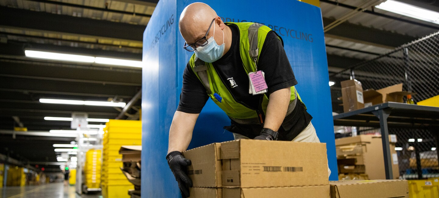 Amazon associate packs or unpacks boxes in a fulfillment center