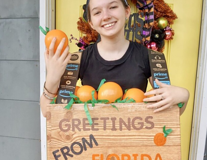 "A young woman wears a Halloween costume that is made of a box around her torso, in wood grain, that says ""greetings from Florida"" on the front. The top of the box is open and shows fake grass and pretend oranges, as though it was a fruit box."