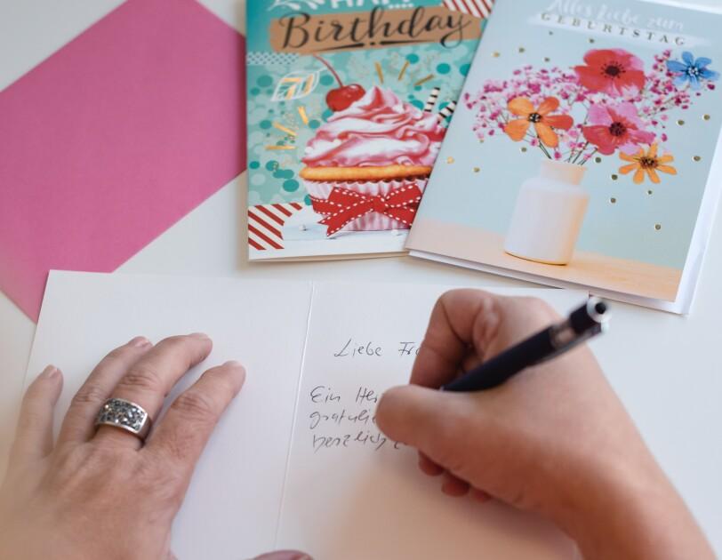 Eine Frau schreibt Postkarten.