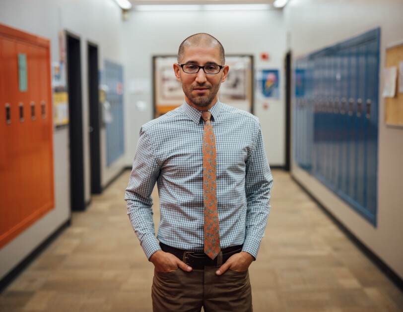 A man in a shirt and tie stands in a school hallway.