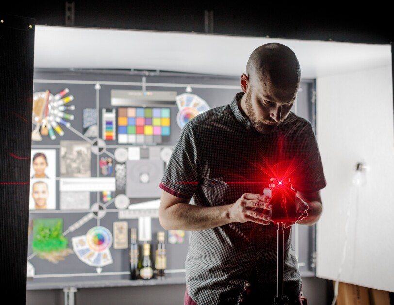 A man leans over a device producing a brightly glowing reddish orange flare of light and a sharp line of light extending to the left of the image. In the background is an illuminated chart.