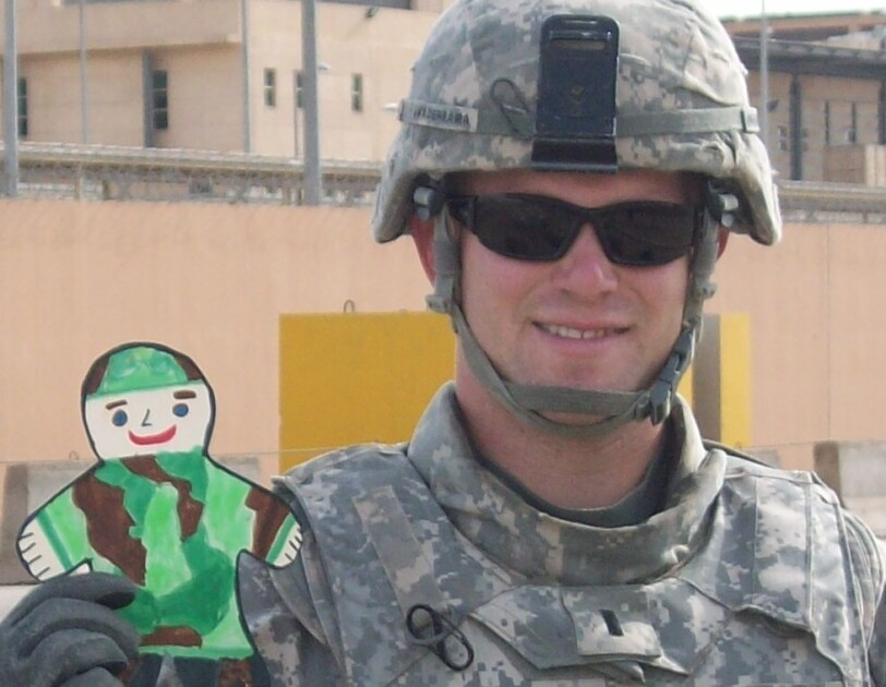Aaron Guaderrama in combat uniform, holding a child's paper cutout of a soldier in camouflage
