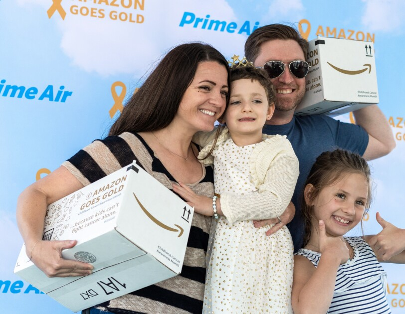 A family of four poses in front of a Prime Air + Amazon Goes Gold backdrop. The family is made up of a mother, father, and two daughters. The parents each hold a white Amazon Goes Gold box.