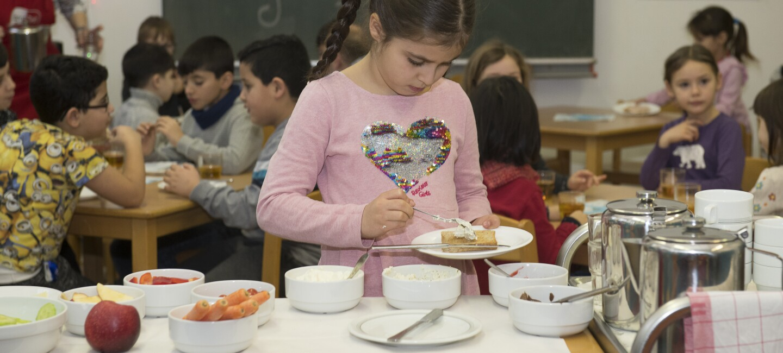 Ein kleines Mädchen in rosa T-Shirt steht an einem Frühstücksbuffet