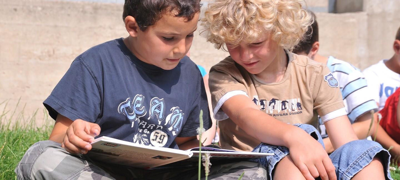 Zwei kleine Jungs sitzen auf der Wiese und lesen gemeinsam in einem Buch.