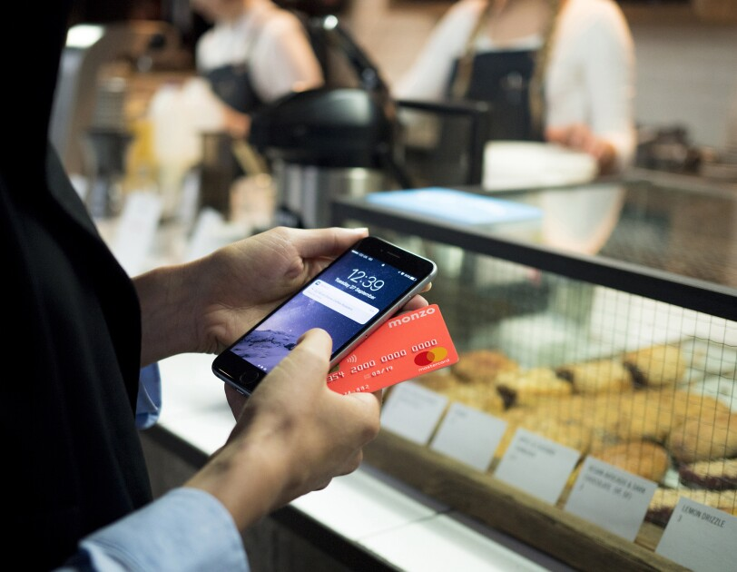Person holding their Monzo card and phone to pay in a bakery