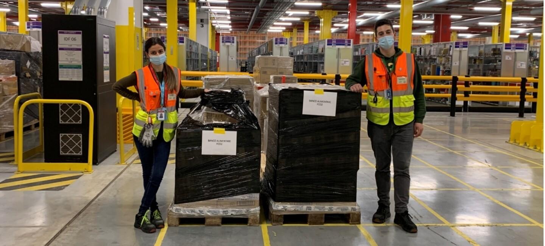 Due dipendenti Amazon, un uomo e una donna, posano accanto a due pallet di materiale destinato a Banco Alimentare. La donna posa sulla sinistra, mentre l'uomo sulla destra. Il materiale sui pallet è ricoperto da una pellicola nera. Entrambi indossano giubbini catarinfrangenti arancioni e gialli e una mascherina chirurgica sul volto. Si trovano all'interno di un magazzino Amazon e sono ripresi a figura intera.