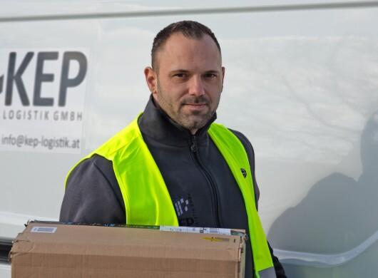 Ein Mann mit Bart in gelber Sicherheitsweste steht vor einem weißen Liefer-Van mit Aufdruck KEP Logistik GmbH. Er hält ein Paket in der Hand.