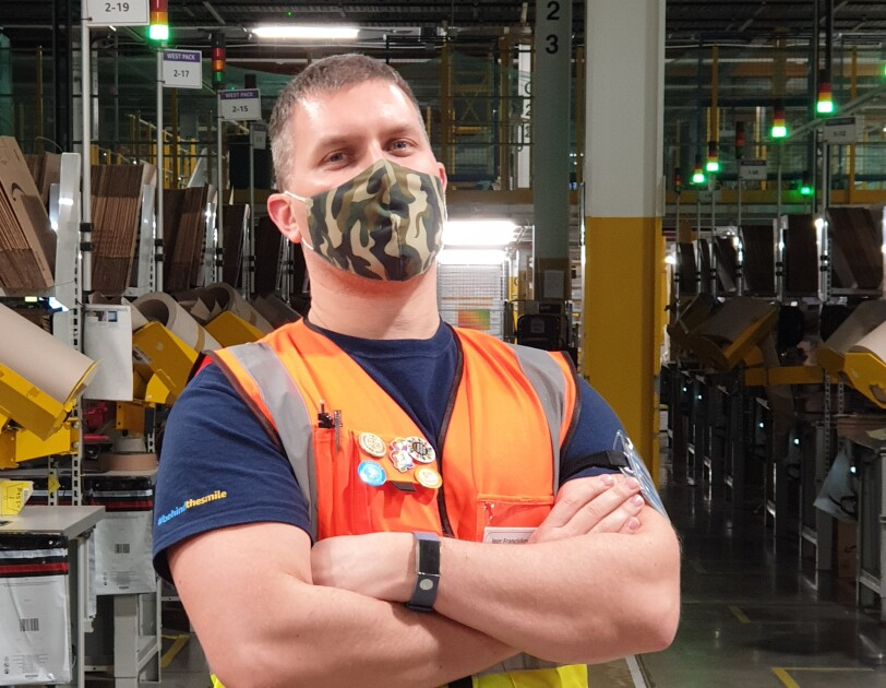 Igor Franciskovity, Area Manager at Amazon's fulfilment centre in Tilbury pictured cross-armed and wearing a high visibility vest and mask, with the shop-floor in the background.
