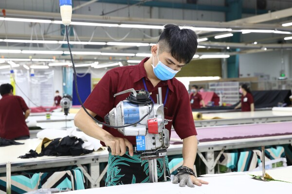 A textile worker uses machinery while wearing mask and safety glove.