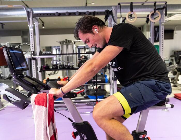 Tiago Moreira-Rato pedaleando para cumplir el reto. En un gimnaso está Tiago montado un bicicleta estática y escuachando música, Tiene un toalla apoyada en el manillar.