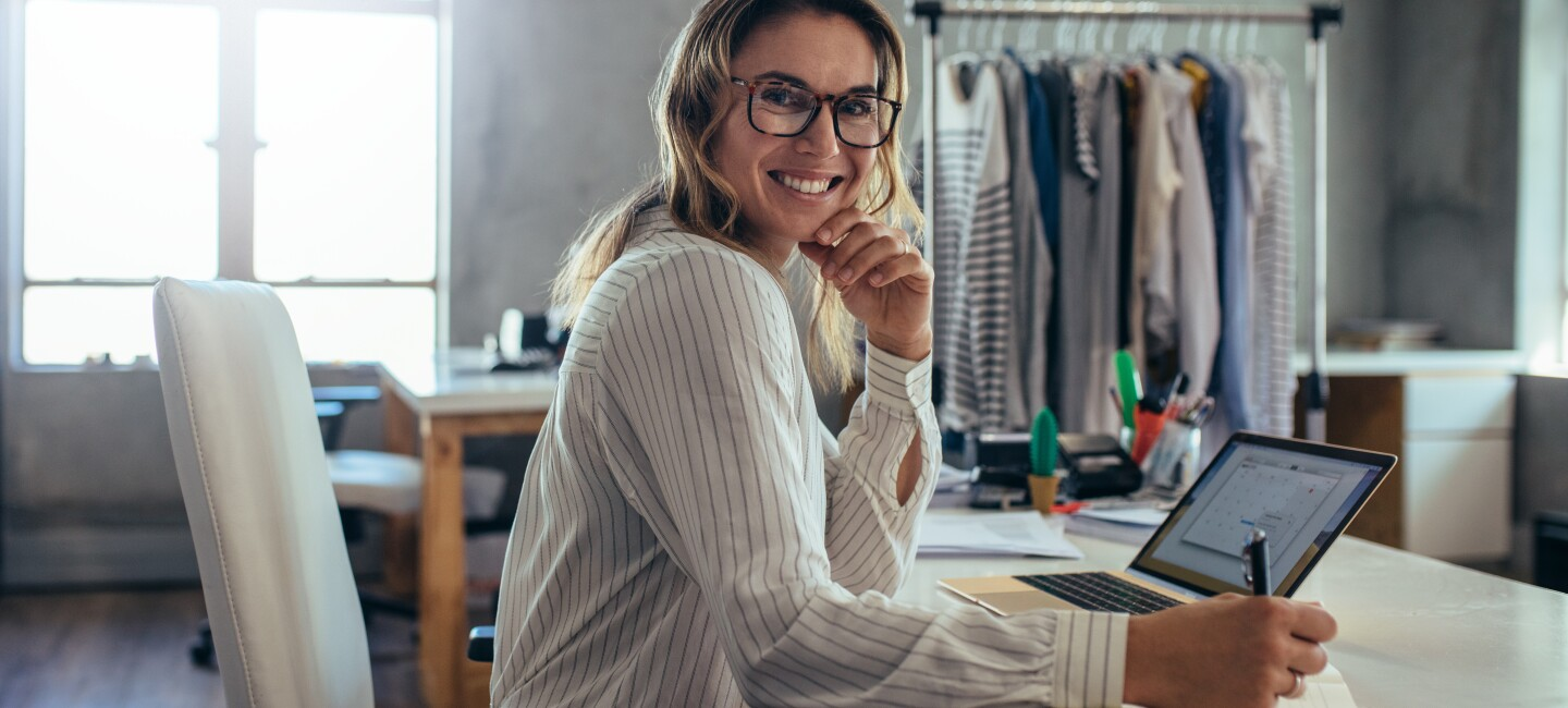 Smiling young woman taking note of orders from customers. Dropshipping business owner working in her office.