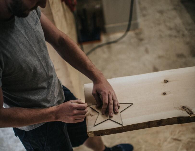 Ein Mann zeichnet einen Holzstern auf einer Holzplatte nach. Er schaut konzentriert auf den Stift in seiner Hand.