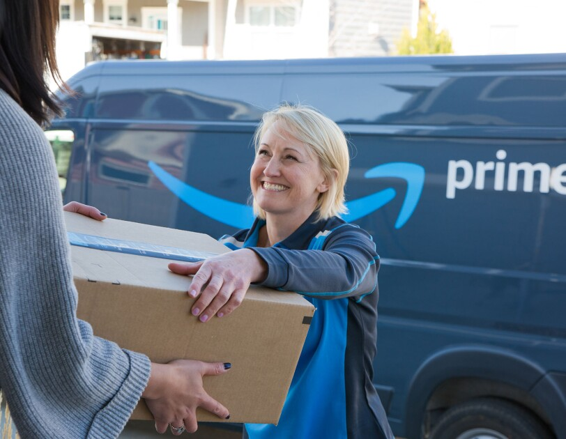 A woman delivers a box to another woman. The delivery driver stands in front of an Amazon DSP van.