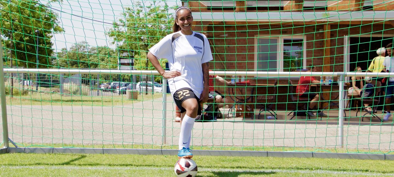 Eine dunkelhäutige Fußballerin vor einem Tor: Sie trägt ein weißes Sportshirt, ihr Fuß ist locker auf einem Ball abgelegt.