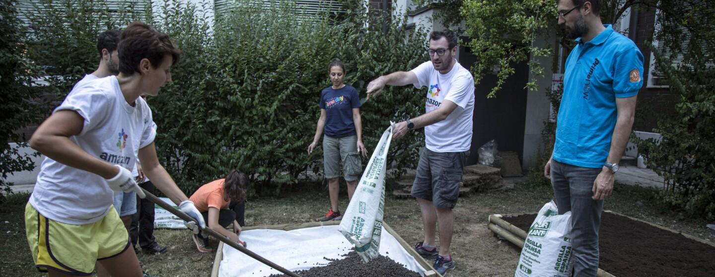 A scuola di verde: sei volontari Amazon all'opera nel giardino della scuola Media Leonardo da Vinci di Affori, nella periferia di Milano. Una donna in primo piano regge una pala con cui stende della terra, versata da un sacco da un uomo, in piedi di fronte alla donna. Gli altri 4 volontari osservano la scena.