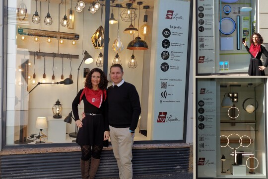Ein Mann und eine Frau stehen vor einem Schaufenster, in dem viele unterschiedliche Lampen zu sehen sind. Beide lächeln in die Kamera.