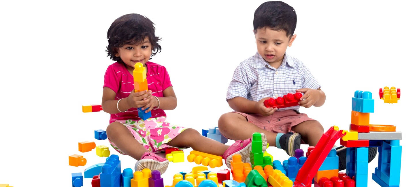 A little girl and boy play with colorful building blocks placed in front of them
