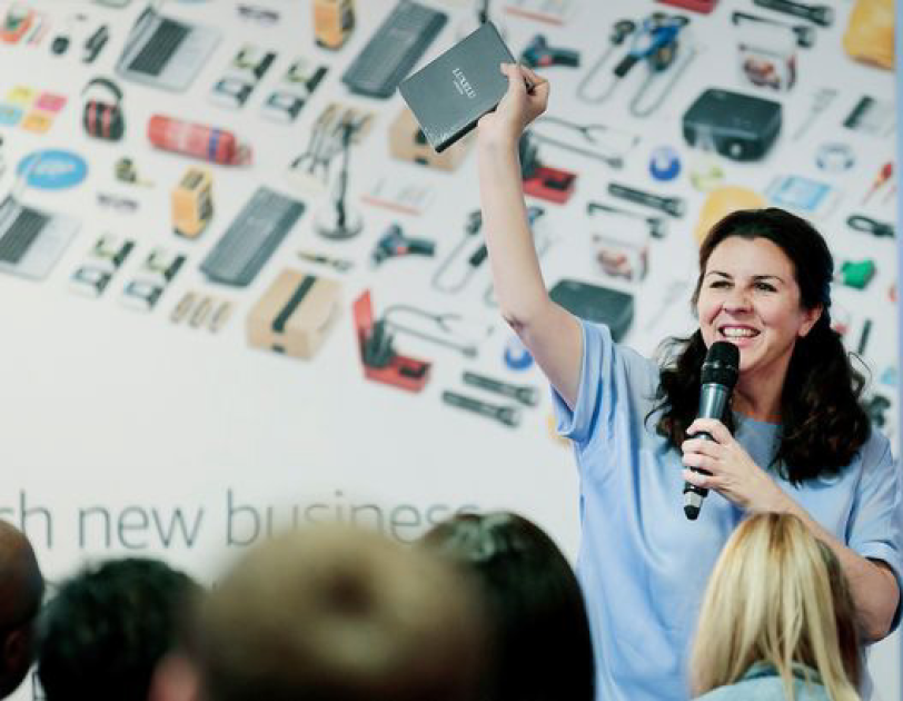 Woman with brown hair holding a mic and talking to an audience