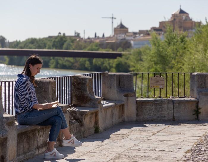 Sonia Llamas es de Córdoba y se encuentra sentada en un puente del Guadalquivir con una libreta en la mano e ilustrando alguna de sus creaciones que pronto venderá en Amazon. Con el pelo largo, una camisa a rayas blanca y azul y unas deportivas blanca. De fondo el río Guadalquivir y parte de la silueta de la ciudad de Córdoba.