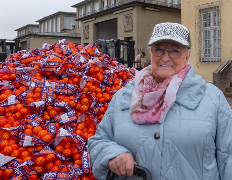 Eine ältere Dame mit Brille und Schildmütze im hellblauen Steppmantel steht vor einem großen Berg von Mandarinen und Orangen.