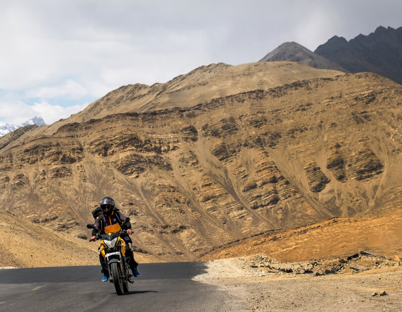 A motorcyclist rides on an asphalt road. Behind him, the road curves to the right and disappears from view. In the background a tan rock formation rises up from the road.