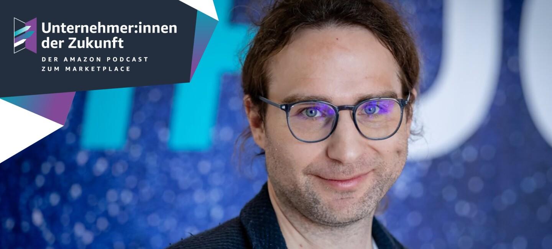 Ein Mann mit braunen langen Haaren und einer Brille lächelt in die Kamera.