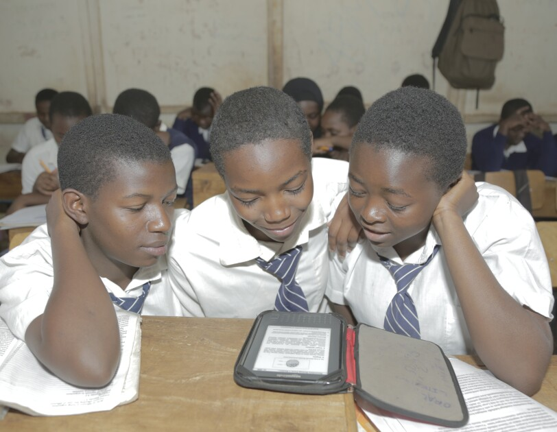 Three boys in school uniforms of white shirts and blue and white striped ties read a Kindle Worldreader.