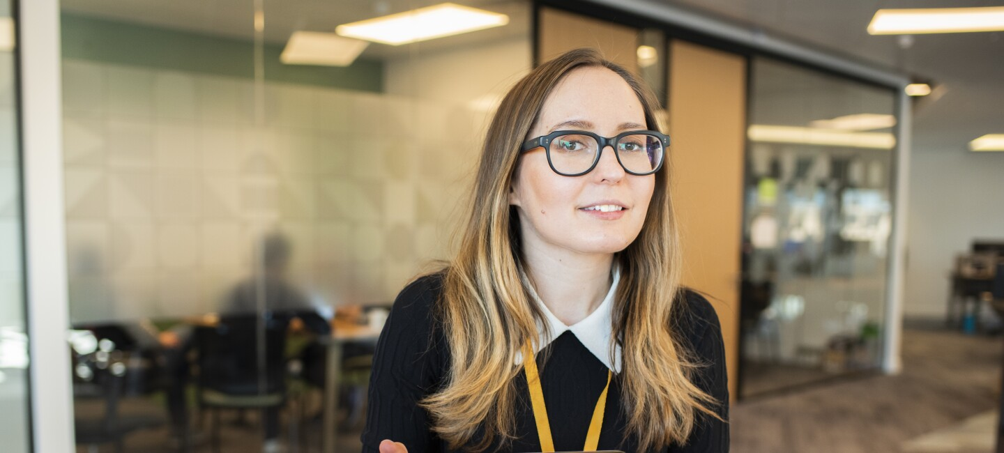 Female employee wearing glasses and sat in an Amazon office