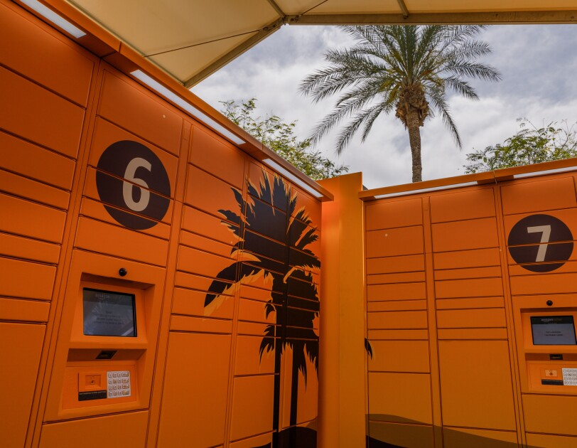 Amazon Lockers decorated with palm tree designs. A real palm tree is in the background. The Lockers are covered by a tent.