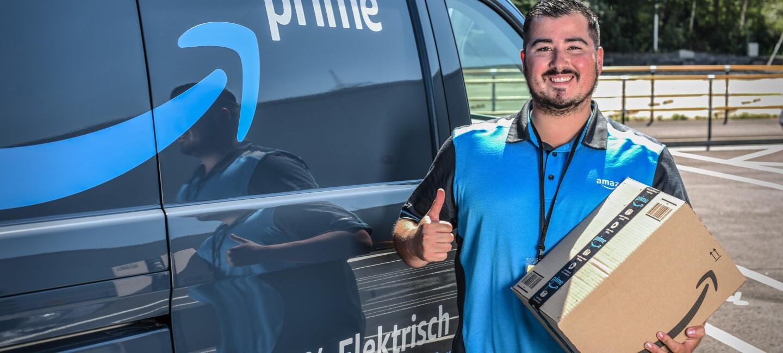 Ein lächelnder junger Mann in Amazon Shirt steht vor einem Prime Lieferfahrzeug. Er hält ein Amazon Paket in der Hand.