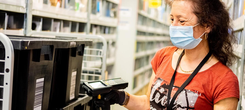 Amazon Mitarbeiterin mit Maske und Handschuhen kommissioniert Artikel im Logistikzentrum