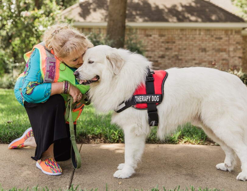 A woman in a bedazzled Amazon Flex vest hugs a white dog, wearing a therapy dog service animal vest.