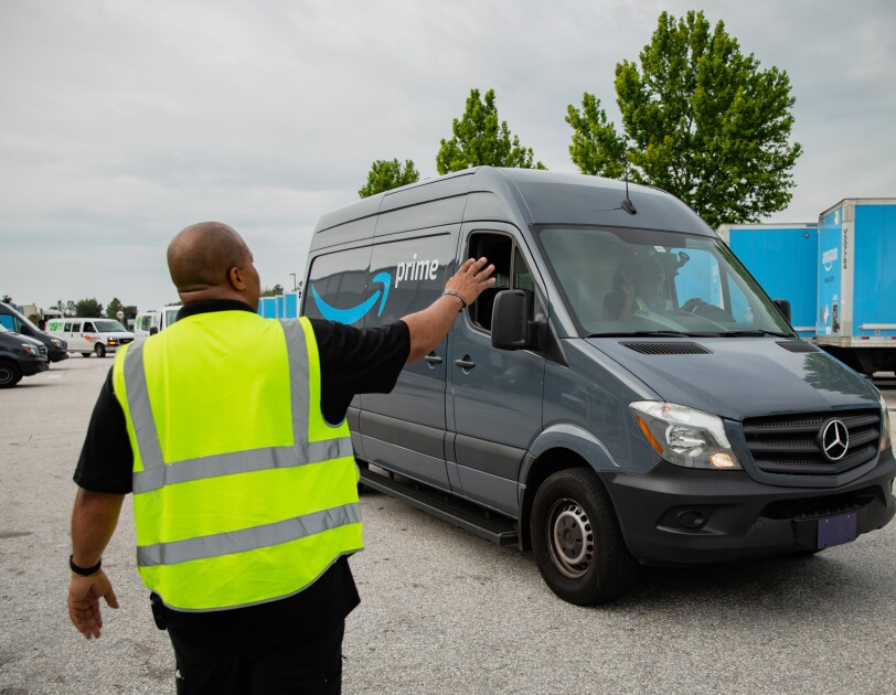 A man in a safety vest waves to a passing van.