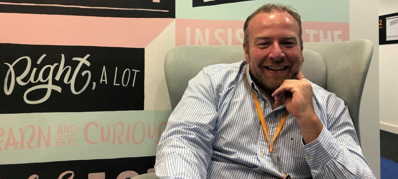 Gerrit bei Amazon. Er sitzt auf einem grauen Sessel. Im Hintergrund sieht man eine bunte Wand mit den Leadership Prinzipen in verschiedene Schriftzügen.