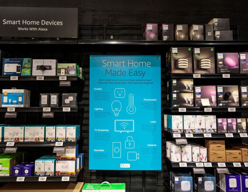 Smart Home Devices displayed in Amazon 4-star store. On a wall display, are outlets, thermostats, lighting, television streaming devices, doorbells, caperas and locks that are all able to connect digitally to Alexa-enabled devices.