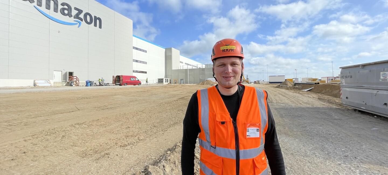 Daniel mit Helm und Sicherheitsweste vor dem neuen Logistikzentrum in Gera.