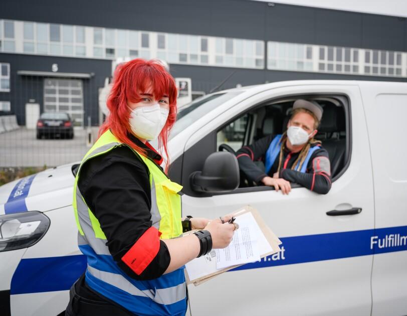 Ein Mann mit roten Haaren und Sicherheitsweste im Gespräch mit einem Lieferfahrer.