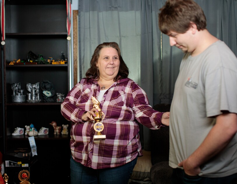 A woman in a plaid shirt holds a trophy. A shelf full of trophies and medals is in the background. To the right of the image, there is a standing man wearing a gray T-shirt.