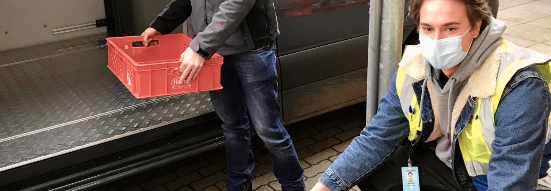 Ein Amazon Mitarbeiter belädt gemeinsam mit einem Tafel-Helfer das Lieferfahrzeug. Beide tragen Masken.