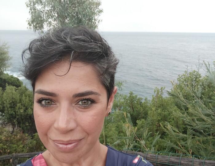 Primo piano di Alessandra, volontaria Amazon. La donna ha i capelli corti e posa sullo sfondo di un ambiente naturale, con il mare alle spalle.