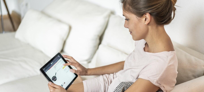 Frauen sitzt auf dem Sofa und bestellt über das Tablet bei Amazon.de