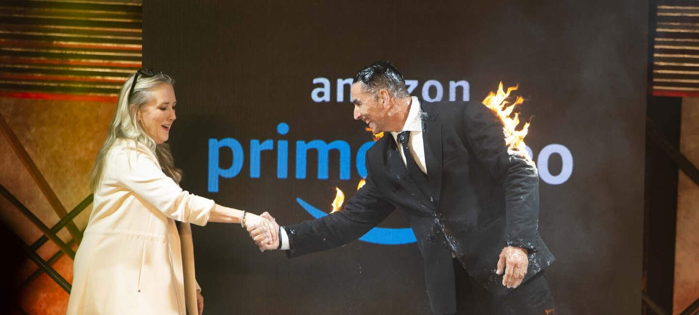 Jennifer Salke in an ivory jacket and dark bottoms shakes hands with Bollywood actor Akshay Kumar. Akshay Kumar has his coat of fire, as he performed a fiery stunt before this hand shake.