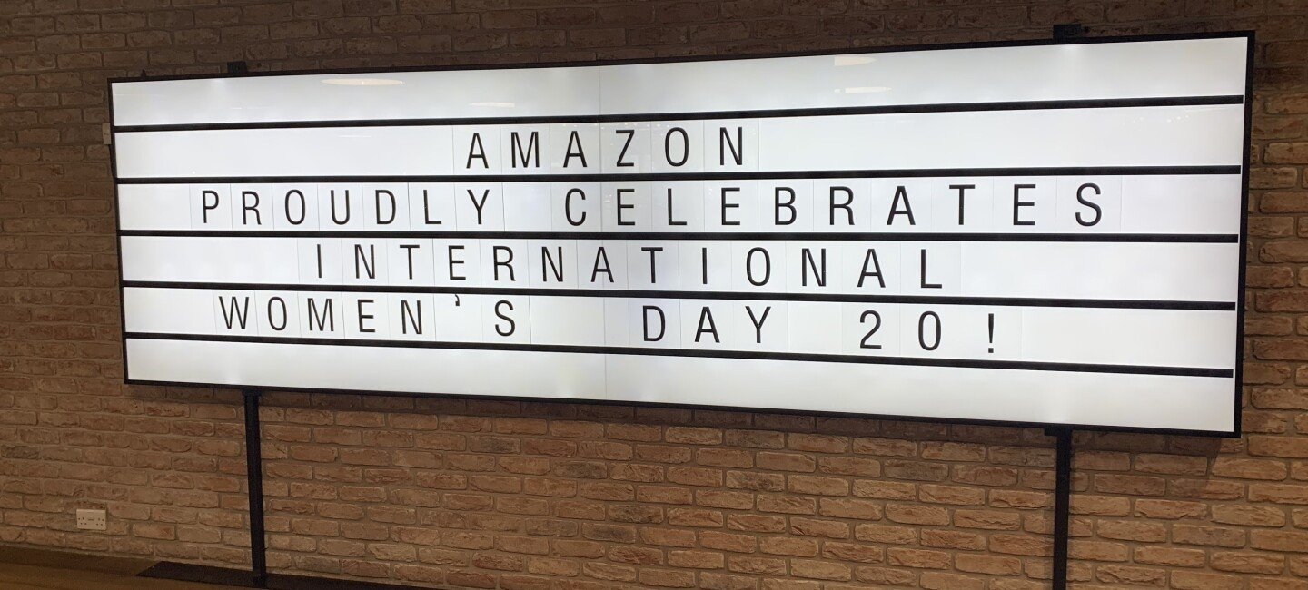 "A large lightbox sign at the Amazon offices reading ""AMAZON PROUDLY CELEBRATES INTERNATIONAL WOMEN'S DAY 20!"". The sign is hanging on a brick wall."